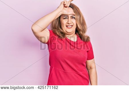 Middle age caucasian woman wearing casual clothes making fun of people with fingers on forehead doing loser gesture mocking and insulting.