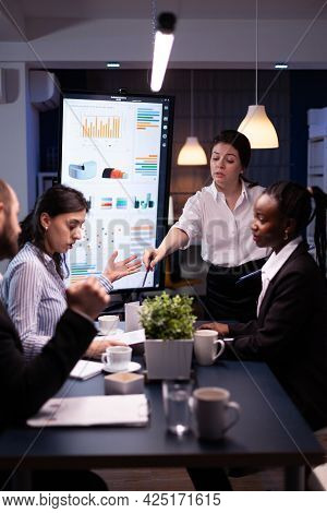 Multi-ethnic Businesspeople Discussing Financial Company Solution Sitting At Conference Table In Mee