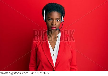 Young african american girl wearing call center agent headset with serious expression on face. simple and natural looking at the camera.