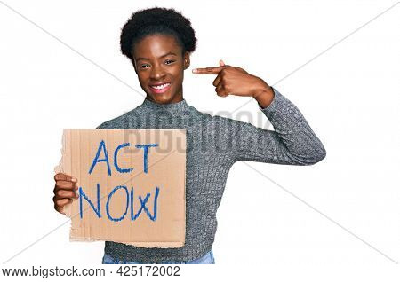 Young african american girl holding act now banner pointing finger to one self smiling happy and proud