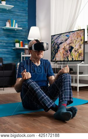 Senior Man Wearing Virtual Reality Headset Practicing Meditation Exercise Sitting On Yoga Mat In Liv