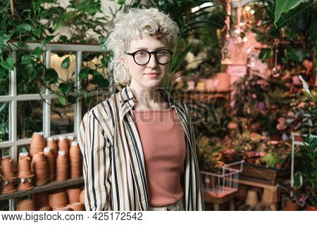 Portrait Of Young Saleswoman In Eyeglasses Looking At Camera While Working In The Garden With Plants