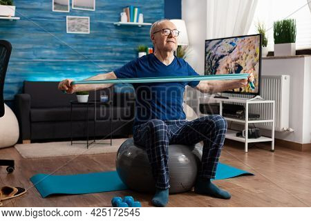 Cheerful Retired Senior Man Exercising Arm Muscles Using Resistance Elastic Band Practicing Aerobic