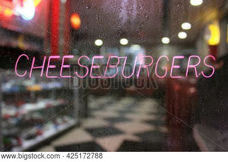 Rainy Window Of Diner With Neon Cheeseburgers Sign