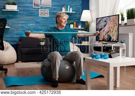 Retired Senior Man Sitting On Fitness Swiss Ball In Living Room Doing Wellness Fitness Workout Strec