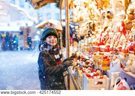 Little Cute Kid Boy Selecting Decoration On Christmas Market. Beautiful Child Shopping For Toys And
