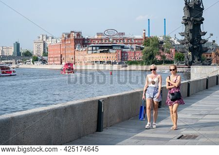 Moscow. Russia. June 26, 2021. Two Young Girls In Light Clothes And Sunglasses Walk Along The River