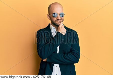 Young hispanic man wearing fashion sunglasses and business jacket thinking concentrated about doubt with finger on chin and looking up wondering