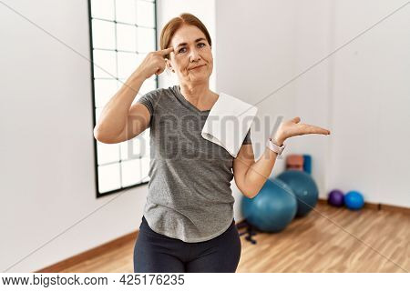 Middle age woman wearing sporty look training at the gym room confused and annoyed with open palm showing copy space and pointing finger to forehead. think about it.