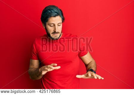 Young hispanic man wearing casual red t shirt disgusted expression, displeased and fearful doing disgust face because aversion reaction.