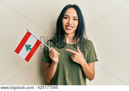 Young hispanic girl holding lebanon flag smiling happy pointing with hand and finger