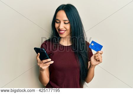 Young hispanic girl holding smartphone and credit card smiling with a happy and cool smile on face. showing teeth.