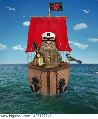 A Beige Cat Captain In A Sailor's Hat With A Bottle Of Rum Is On A Sailboat With A Red Sail On The S
