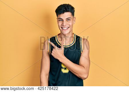 Young hispanic man wearing basketball uniform cheerful with a smile of face pointing with hand and finger up to the side with happy and natural expression on face