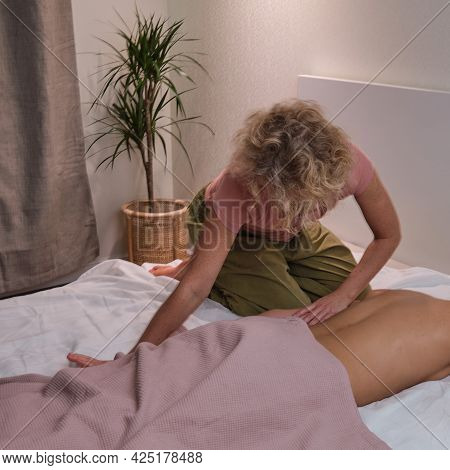 A Woman Does A Holistic Back Massage On A Home Bed In The Bedroom. Blonde Masseuse On The Couch Mass