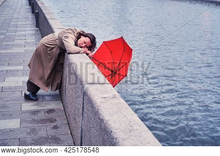 An Unhappy Woman With A Red Umbrella On The Embankment By The River
