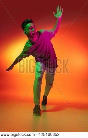 Portrait Of Caucasian Young Man Dancing, Dancing Isolated On Orange Studio Background In Neon Light.