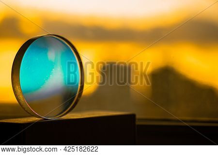 Transparent Round Glass Sphere With Blue Reflection On A Bright Yellow Light Back Of The City By The