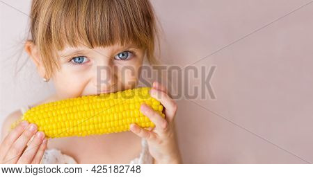 Close-up Portrait Of A Little Beautiful Girl With Blue Eyes And Boiled Corn In Her Hands, Girl Bitin