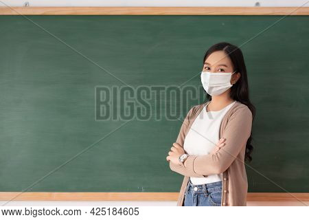 Portrait Of Young Female Teacher With Arms Crossed Wearing Protective Face Mask Standing Over Chalkb