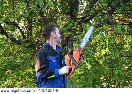 Strong, Confident Man Holds A Chainsaw In His Hands. A Woodcutter In Work Clothes With A Saw On A Tr