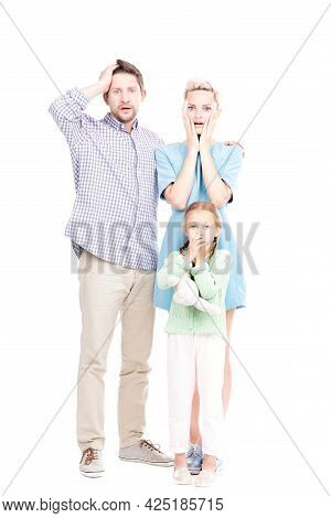 Vertical Full Length Shot Of Modern Man And Woman Standing With Their Little Daughter Astonished At
