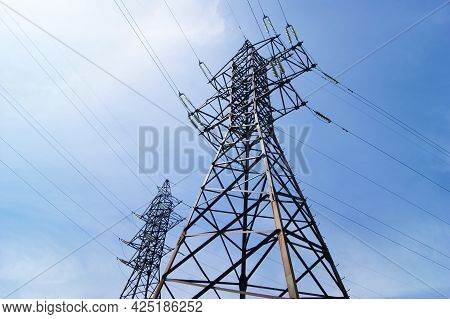 Electricity Pylon, Electrical Transmission Tower, Against Blue Sky Background.