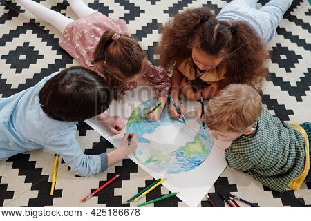 Cute kids drawing planet on large paper while lying on the floor