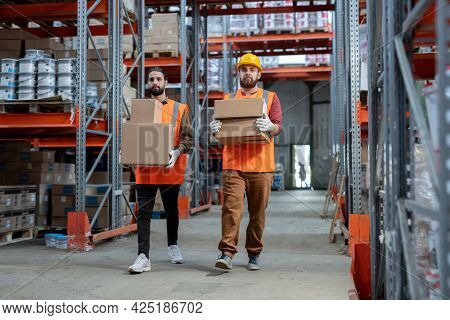 Two loaders in workwear carrying boxes with goods