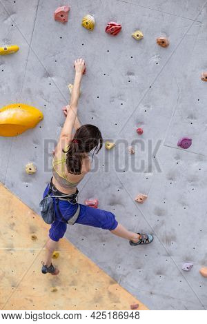 Smiling Girl Climbs The Climbing Wall, The Woman Is Engaged In Extreme Sports, Rock Climbing In The