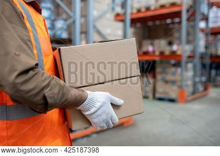 Warehouse engineer in workwear carrying boxes with goods