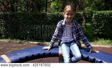 Blonde Girl Playing At Playground, Child Spinning, Rotating On Merry-go-round In Park, Face Of Happy