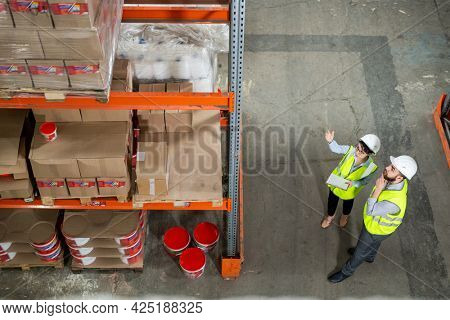 Two workes of warehouse in uniform having discussion in front of rack with packed goods