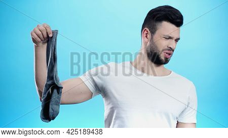 Man Feeling Disgusted While Holding Smelly Sock Isolated On Blue