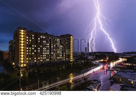 A Lightning Strike During A Thunderstorm Against The Background Of A City Building. Night City Traff