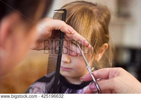The Hands Of A Hairdresser With A Comb And Scissors Make A Fashionable Modern Haircut For A Girl For