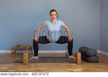 Pregnant Woman Standing In Sumo Squat Exercise, Goddess Pose
