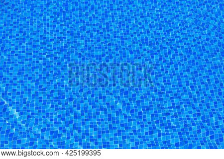 Water Ripples On Blue Tiled Swimming Pool Background. Blue Turquoise Pool Water. Ripples Lit Up By T