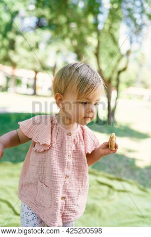 Little Girl Walks On A Green Lawn With A Pancake