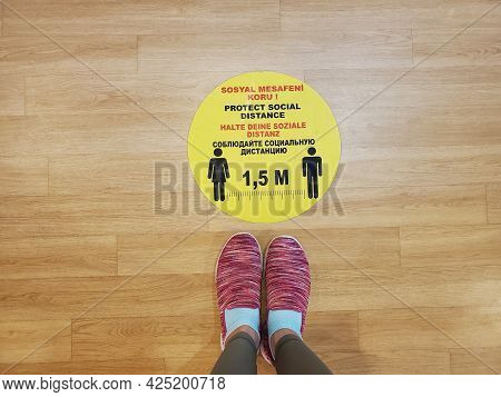 Pov Feet Wearing Pink Sport Shoes Stand By Yellow Sticker Warning Of Keeping Social Distance In Turk