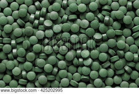 Spirulina Pills Background. Green Tablets Superfood. Flat Lay, Top View