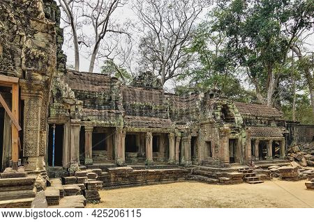 Ruins Of A Temple In The Ancient City Of Angkor. A Dilapidated Roof And Galleries With Columns. Bas-