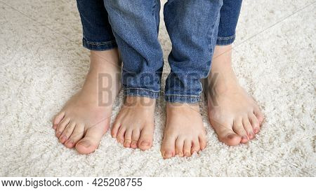 Closeup Of Female And Child Feet Standing On Soft Carpet And Moving Toes