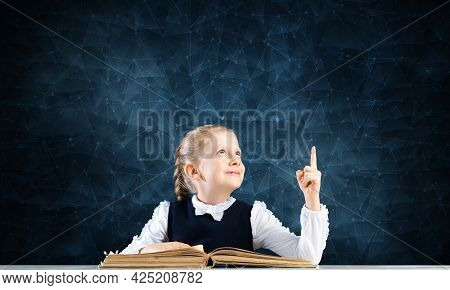 Smiling Little Girl Sitting At Desk With Open Book. Research And Education In School. Happy Schoolgi
