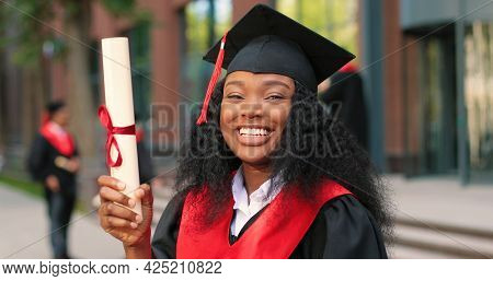 School Graduate Woman In Academic Gown And Hat Looking At The Camera With Happy Smile. Happy Multira