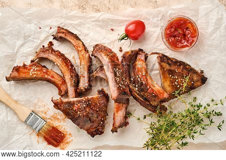 Grilled And Smoked Pork Ribs With Barbeque Sauce On An Old Vintage Wooden Cutting Board On Old Concr