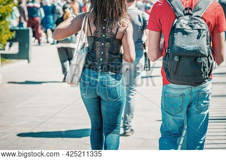 Abstract Unrecognizable Girl And Guy In Jeans, Rear View Close-up, Walking In City
