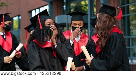 Unforgettable Emotions. Waist Up Portrait Of The Group Of Students At The Graduation Gowns And Caps