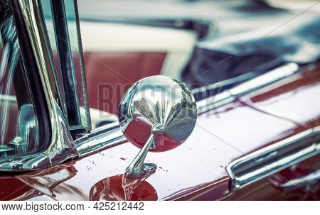 Close up shot of shiny side view mirror on a classic car