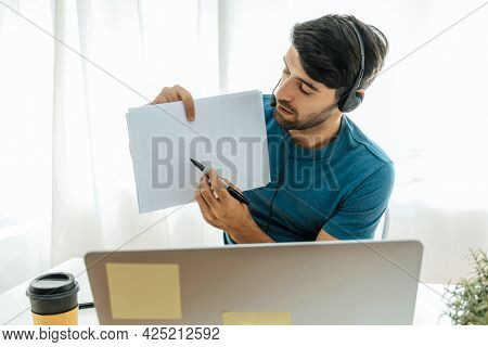E-learning. Handsome Man Teacher Showing Blank Paper Sheet For Teaching Online At Web Camera On Lapt
